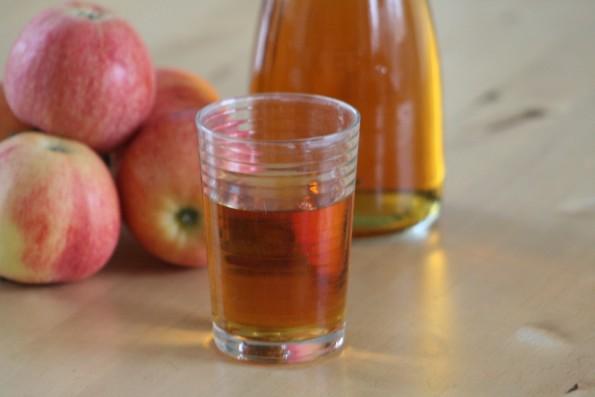 брага из яблок для самогона в стакане на столе