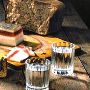 очищенный хлебом самогон, хлеб и сало на столе
