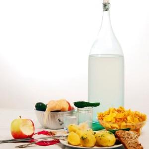 самогон из сока и закуска на столе