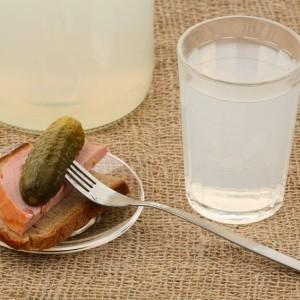 мутный самогон в стакане и закуска