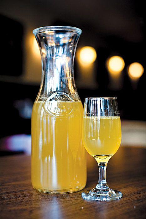 Вино из лимонов в бокале и бутылке